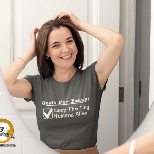 """Woman preparing for her day wearing a t-shirt with """"Goals For Today: Keep Tiny Humans Alive"""""""