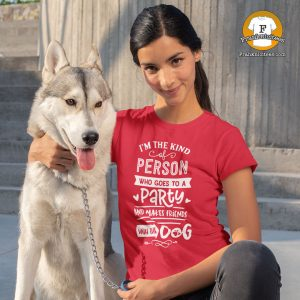 """A dog with a woman wearing a shirt that says """"I'm The Type Of Person who goes to a party and makes friends with the dog"""""""