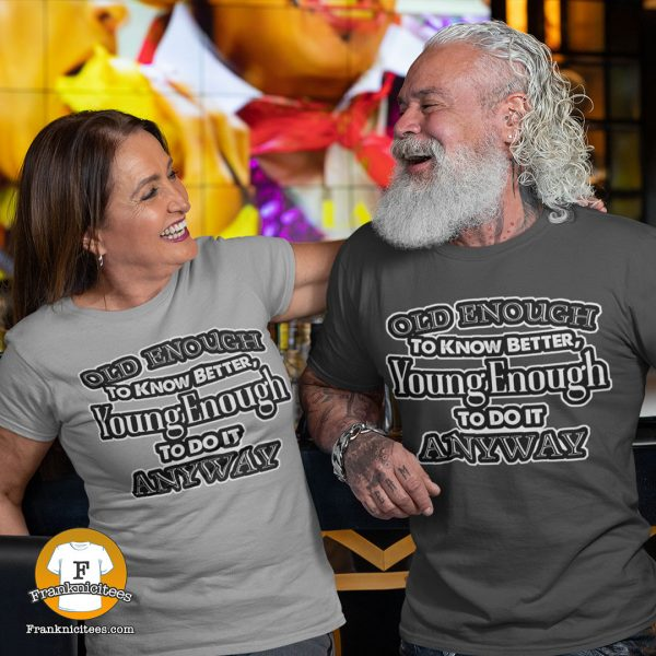 "Couple wearing t-shirts that say ""Old Enough To Know Better, Young Enough To Do It Anyway"""